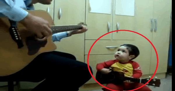 un enfant joue de la guitare avec son père